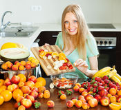 Ordinary long-haired  girl cooking fruit salad Stock Photography