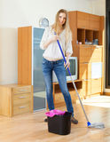 Ordinary long-haired girl washing  floor with mop Royalty Free Stock Photography