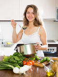 Ordinary long-haired  woman cooking  soup Royalty Free Stock Photo