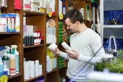 Ordinary male customer buying flea treatment and shampoo Stock Photos