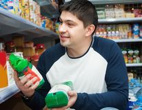 Customer standing near shelves with food. Ordinary male customer standing near shelves with food at shop Stock Image