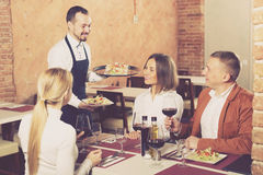 Ordinary male waiter carrying order for visitors Stock Photography