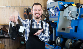 Ordinary male worker showing fixed shoes. In shoe repair workshop Royalty Free Stock Image