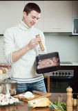 Ordinary man cooking meat with  mushrooms and potatoes Stock Image