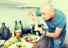 Ordinary man sprinkle with pepper salad on plate Royalty Free Stock Photography