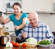 Ordinary mature couple cooking together Royalty Free Stock Image