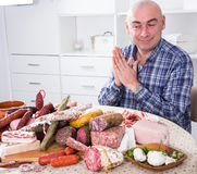 Ordinary men with lots of meat and sausage products. Portrait of ordinary man with lots of meat and sausage products stock photo