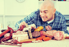 Ordinary men with lots of meat and sausage products. Portrait of ordinary man with lots of meat and sausage products Royalty Free Stock Image