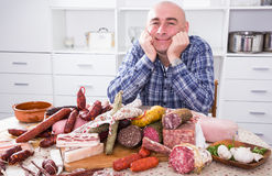 Ordinary men with lots of meat and sausage products. Portrait of ordinary man with lots of meat and sausage products Stock Photography