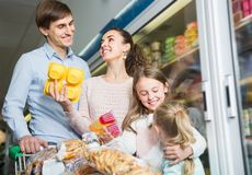 Ordinary parents with two kids holding purchases in store. Average ordinary parents with two kids holding purchases in store Stock Photos