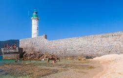 Ordinary people swimming near white lighthouse Stock Photo