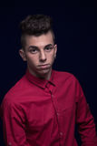 Ordinary portrait, one teenager boy, red shirt, Caucasian, dark. Background, looking to camera Royalty Free Stock Photos