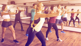 Ordinary positive people learning zumba steps. In dance hall Stock Images