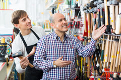 Ordinary positive smiling customer and  seller choosing hammer Royalty Free Stock Photos