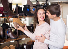 Ordinary smiling couple shopping at shoe store Royalty Free Stock Images