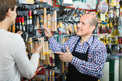 Ordinary smiling customer and friendly seller choosing hammer Stock Image