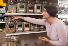 Woman buyer selects herbs in store of ecological products. Ordinary woman buyer selects herbs in store of ecological products Stock Image