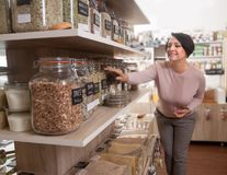 Woman buyer selects herbs in store of ecological products. Ordinary woman buyer selects herbs in store of ecological products Stock Images