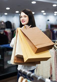 Ordinary woman buyer with shopping bags. At clothing store Royalty Free Stock Photo