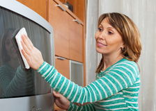 Ordinary woman cleaning TV Stock Photo