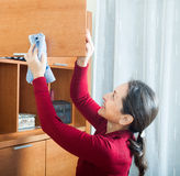 Ordinary  woman cleaning wooden furniture Royalty Free Stock Images