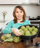 Ordinary woman cooking artichoke Stock Image