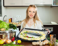 Ordinary woman cooking fish and potato in sheet pan Stock Images