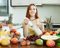 Ordinary woman cooking milkshake with fruits Royalty Free Stock Images