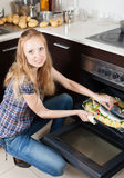 Ordinary woman cooking raw fish in oven. At home kitchen Stock Images