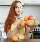 Ordinary woman holding plate with ripe mango Stock Photo
