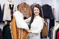 Ordinary woman looking at jacket Stock Photography