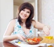 Ordinary woman pours oil to veggie salad Royalty Free Stock Photos