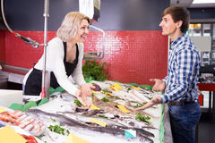 Ordinary woman selling fish to male customer in store. Mature ordinary women selling fish to male customer in store Stock Image