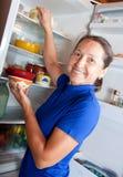 Ordinary woman taking something of the fridge Royalty Free Stock Photos