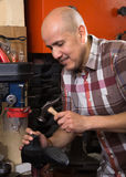 Ordinary workman sewing leather boots on stitch lathe in worksho Royalty Free Stock Photos