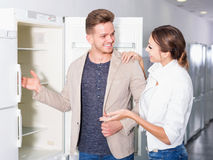 Ordinary young customers looking at fridges Stock Image