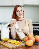Ordinary young woman making beverages with blender from mango Stock Photo