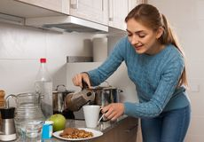 Ordinary young Woman preparing coffee in the kitchen at home stock image