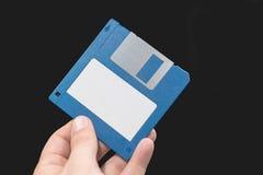 Ordinateur à disque souple à disposition sur le fond noir Image stock