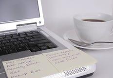 Ordinateur avec des notes et cuvette de café Photographie stock
