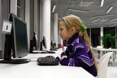 Ordinateur d'utilisation de petite fille dans une bibliothèque Images libres de droits