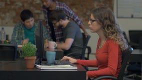 Ordinateur de dactylographie de femme, gens d'affaires de bureau de bureau se reposant de groupe banque de vidéos