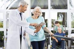 Ordinateur de docteur Showing Reports On à la femme au centre de fitness Images stock