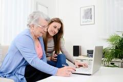 Ordinateur de enseignement de jeune femme gaie à une vieille femme supérieure à la maison Images stock