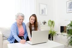 Ordinateur de enseignement de jeune femme gaie à une vieille femme supérieure à la maison Photos stock