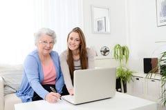 Ordinateur de enseignement de jeune femme gaie à une vieille femme supérieure à la maison Image libre de droits