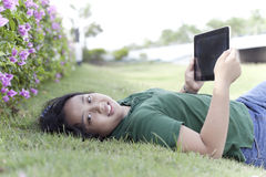 Ordinateur de fille et de comprimé sur l'herbe verte Photographie stock libre de droits