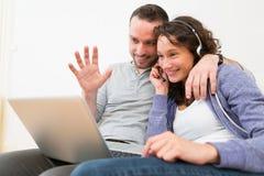 Ordinateur de invitation visuel de jeunes couples heureux Images stock