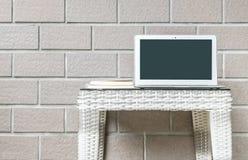 Ordinateur de plan rapproché sur la table en bois brouillée d'armure et fond brun de texture de mur de briques, bel intérieur de  Photo stock