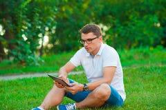 Ordinateur de tablette de fixation de jeune homme Photos stock